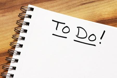 springboard: En blanco con textura p�gina en blanco de un port�til de espiral sobre fondo de madera, listos para el texto. Foto de archivo