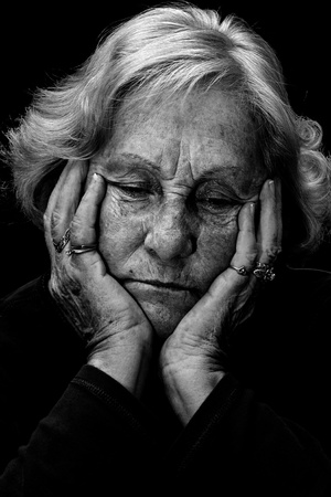 doom: In a dark place: Dramatic exagerated low key portrait of an elderly woman looking very depressed and alone.
