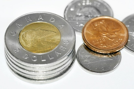 Stack of two dollar canadian coins with focus on the polar bear with other coins around including a copper cent with maple leaf. photo