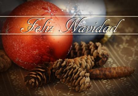 navidad navidad: Grungy holiday theme: Feliz Navidad text over old vintage glass Christmas ornament on dark brown wallpaper with pine cones.