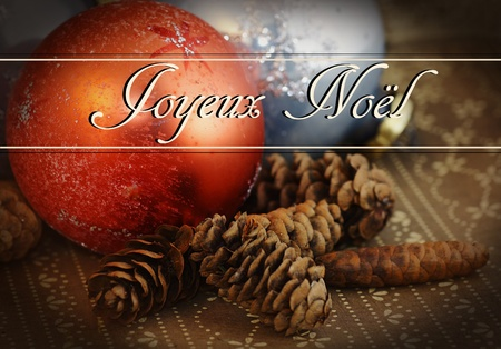 joyeux: Grungy holiday theme: Joyeux Noel text over old vintage glass Christmas ornament on dark brown wallpaper with pine cones.