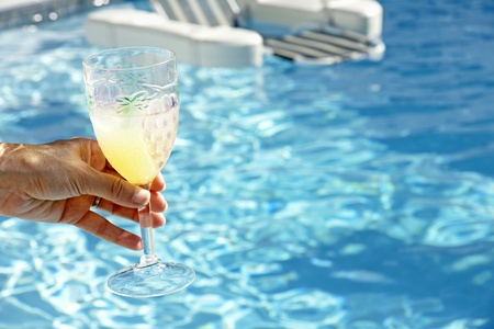 drank: Join the fun and relaxation: womans hand handing over a refreshing cocktail to be drank in the beautiful pool water