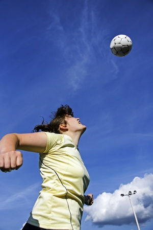 female soccer: Real female soccer or football player during a match, reaching to hit the ball with her head and score a goal with sky and stadium spot lights in background.