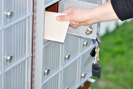 Hand retrieving a letter from the neighborhood mailboxes, can be bill, tax or other mail. Stock fotó