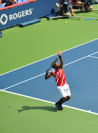 atp: Gael Monfils serving the ball at the Rogers cup 2011 in Montreal, Quebec, Canada, the tennis player is about to spring in the air and hit hard.