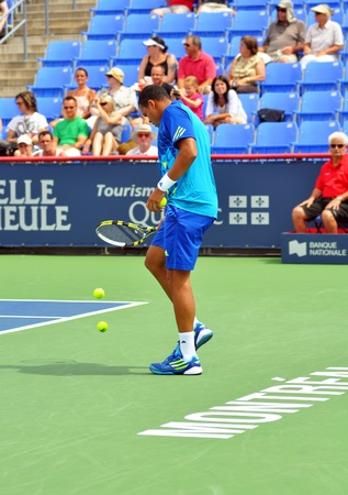Professional tennis player Jo-Wilfred Tsonga picking the ball that defeated Roger Federer at the Masters Rogers cup 2011 in Montreal, Quebec, Canada.