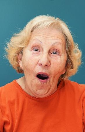 彼女の顔に開いた口と笑顔のヒント面白い驚いた表情で年配の女性。