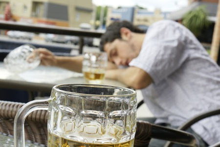 drunk: Alcohol abuse: drunk young man or student lying down on a table with beer bock still in hand, focus on glass up front. Stock Photo