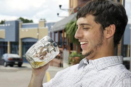 hombre tomando cerveza: Hombre joven o estudiante feliz de saber que sigue siendo la cerveza en el vaso mientras se está sentado al aire libre en la terraza de un bar durante una tarde en la ciudad. Foto de archivo