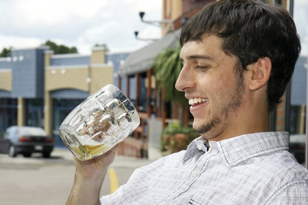 Young man or student happy to find out there is still beer in his glass while sitting outdoor on a bars terrace during an afternoon on the town. photo