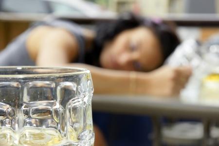 jovenes tomando alcohol: El abuso de alcohol: mujer ebria joven o estudiante se acuesta sobre una mesa con cerveza Bock todavía en la mano, se centran en el vidrio al frente.