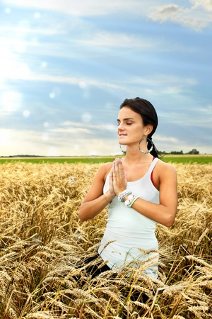 Beautiful healthy young woman connecting with nature by doing yoga and medidating at dawn in a ripe wheat field. photo