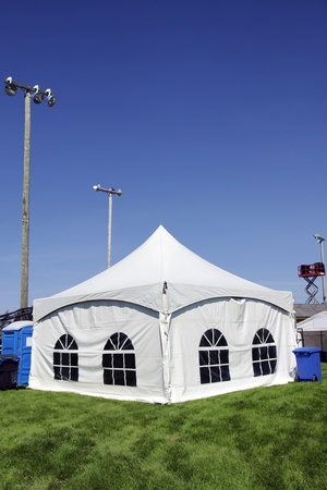 portables: Celebration or event: White tent on soccer field with lighting ready for guests in case of rain with sound system on lift in the background, portable toilet and bins for disposal.