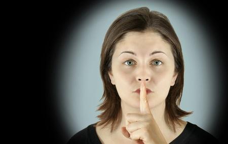 fair skin: Concepto de silencio dram�tico: mujer hermosa piel muy p�lido joven, con impresionantes ojos azules le introduce el dedo en los labios para proteger un secreto, aislado en un fondo azul fr�o con vi�eta negro.