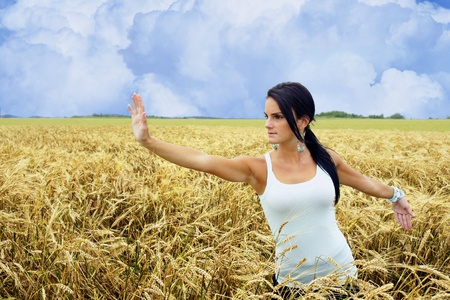High pat on horse single whip tai chi position performed by a young woman connecting with nature while exercising in a wheat field.