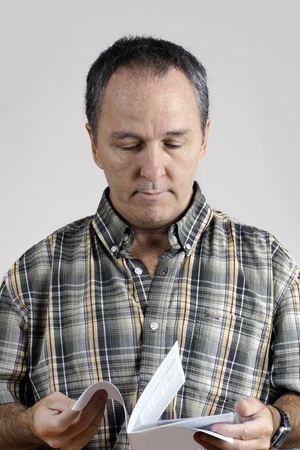 Middle-aged man reading an instruction manual looking puzzled. photo