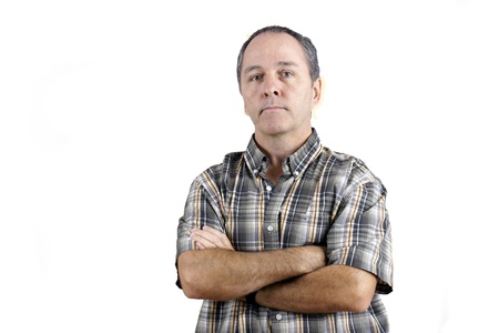 Middle aged caucasian man with doubtful expresssion and arms crossed looking at camera over white background.
