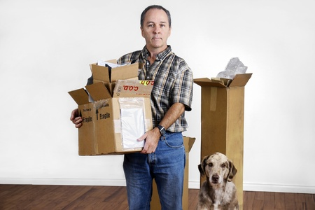 moving out: MIddle age man and dog moving out holding boxes looking sad in empty bare room. Stock Photo