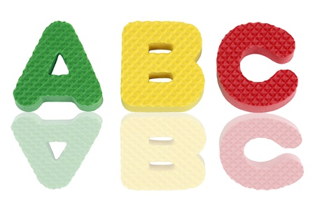 Fun colorful A B C alphabet letters in green, yellow and red textured foam with reflections. photo
