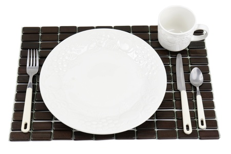 place mat: Dinner plate, white textured China with grapes and tomatoes design over a dark wood place mat.