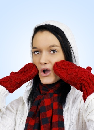 Winter time concept: cute oh my it's cold friendly natural young woman with red mittens and white hoodie over light blue background.