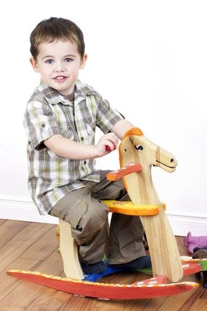 Cute little boy riding a handcarfted wooden rocking horse chair, vertical studio shot.