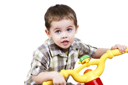 Cute little boy playing by riding a toy bicycle. Stock Photo - 11161550