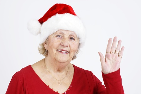 Grand-mother sending her love for Christmas by waving her hand while wearing Santa Claus hat.