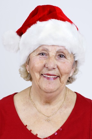 Detailed close-up of a grandmother smiling as she prepares for Christmas with her red Santa Claus hat. Banco de Imagens