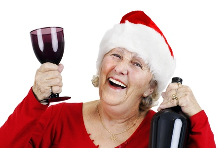 Holiday concept: smiling senior woman or grandmother is wearing Santa Clauss hat and having lots of fun drinking at the Christmas party