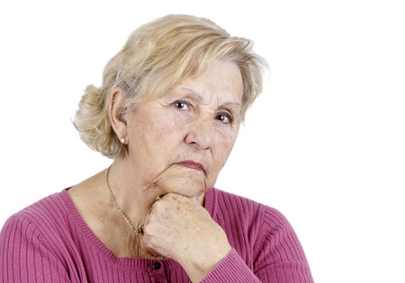 Portrait of a serious senior woman holding her chin looking at the camera, isolated on white. Stock Photo