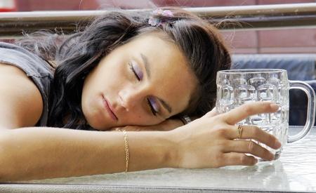 borracho: Mujer joven que duerme al aire libre en la terraza pub después de haber bebido demasiada cerveza. Foto de archivo
