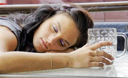 intoxicated: Young woman asleep outdoors on pubs terrace after drinking too much beer. Stock Photo