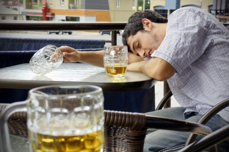 binge: Young man passed out drunk with beer bocks on the glass table of an outdoor terrace: perfect for alcoholism, student hazing, beer binging and other related concepts.