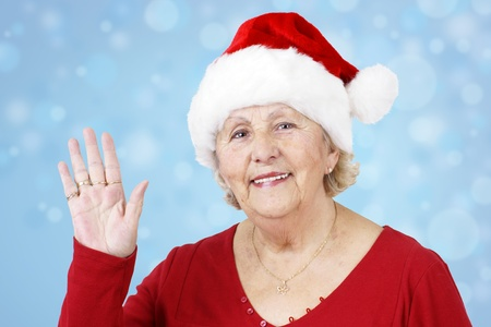 Grand-mother sending her love for Christmas by waving her hand while wearing Santa Claus hat over winter blue background