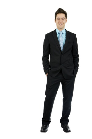 Full body shot of a smiling dashing handsome young man in his business suit with hands in pocket, isolated on white background. photo