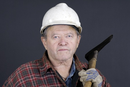 Portrait of an active senior man lumberjack or logger ready to work in the forest with scratched up hard hat, axe, plaid shirt and gloves, great details. photo