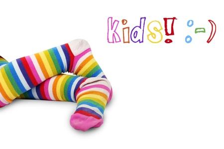 calcetines: Disparo divertido de los pies cruzados de ni�a con calcetines a rayas muy coloridas o medias de m�s de blanco con los ni�os y los s�mbolos cara feliz: ideal para cualquier cosa relacionada con los ni�os. Foto de archivo