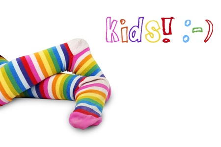 Funny shot of a little girls crossed feet in very colorful striped socks or tights over white with kids and happy face symbols: perfect for anything relating to kids.