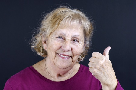 approbation: Portrait of a happy senior woman holding her thumb up in sign of approbation, isolated on black.