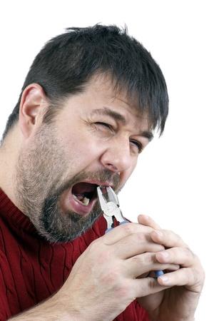 alicates: Hombre de mediana edad tirando es propio diente con un par de alicates aislados en blanco