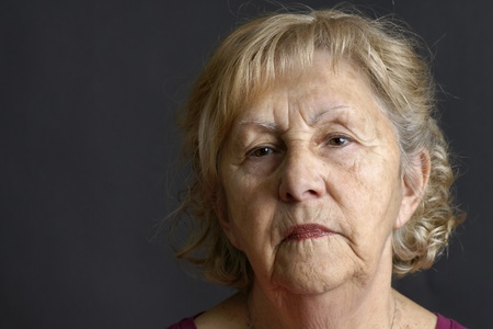 Close-up of a blond senior woman deep in her thoughts over dark background, great details of the aging skin.