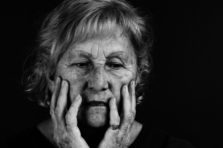 grieving: Creative low key black and white to emphasize dramatic facial expression of senior woman.