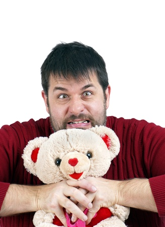 Contrast concept: frustrated or deranged large bearded middle-age man strangling a soft and cuddly generic plush teddy bear. Stock Photo