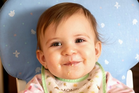Cute and sweet face baby girl eating cereals and making a mess photo