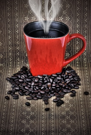 Grungy red ceramic cup or mug filled with steam hot black coffee with beans over vintage brown wallpaper, hdr treament. photo