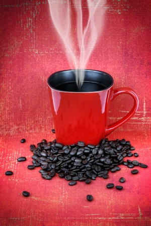 Grungy red ceramic cup or mug filled with steam hot black coffee with beans over vintage red wallpaper, hdr treament.