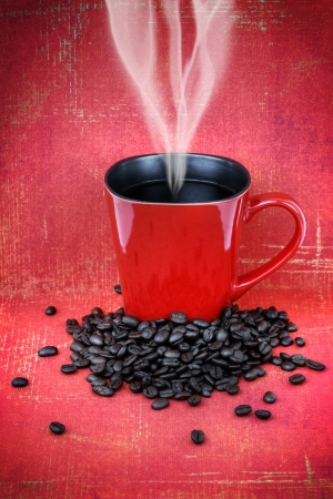good: Grungy red ceramic cup or mug filled with steam hot black coffee with beans over vintage red wallpaper, hdr treament.