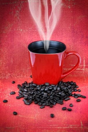 Grungy rode keramische kop of mok gevuld met stoom hete zwarte koffie met bonen over vintage rode behang, hdr treament.