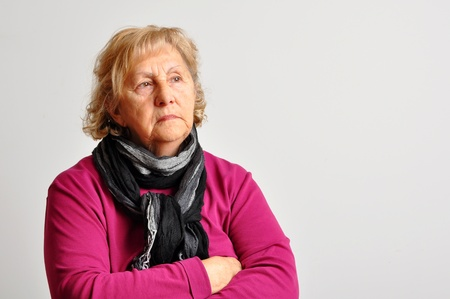 grieving: Blond senior woman with crossed arms deep in her thoughts over light grey background. Stock Photo